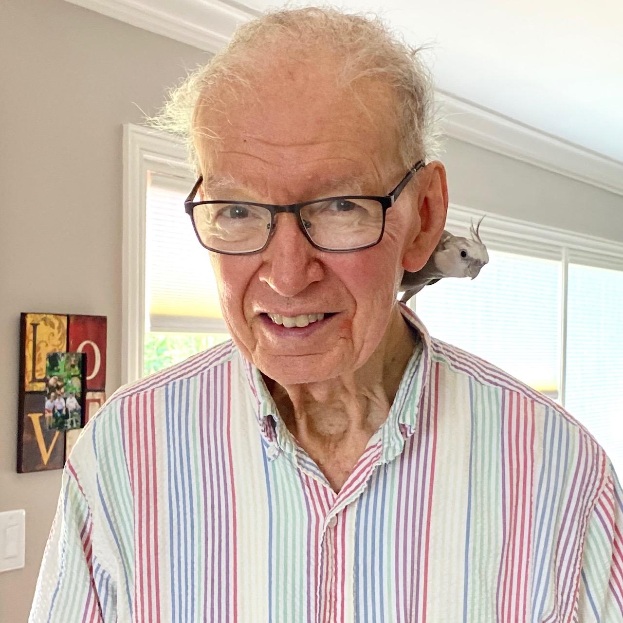 cockatiel sits on grandpa's shoulder