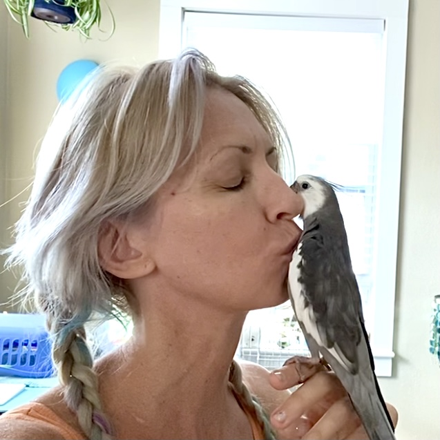 woman kisses cockatiel